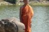 "Monk posing for tourists on the ""Naga"" or symbolic rainbow bridge"