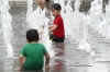 Children play in the fountain in front of Statue of King Sejong the Great in Gwanghwamun Square, Seoul KR