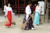 Monks sweeping autumn leaves at the Dazaifu Tenman-gū (shrine), Japan